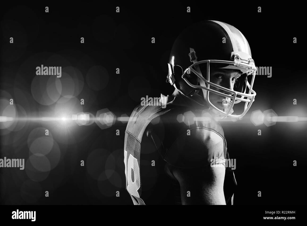 Giocatore di football americano nel casco in piedi su sfondo nero Immagini Stock