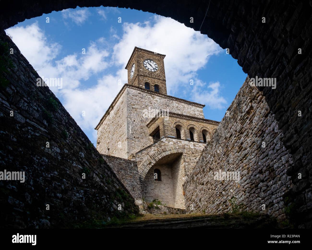 Interessante il framing attraverso il passaggio a volta del clock tower della fortezza di Argirocastro in Albania, con un cielo blu e nuvole bianche sullo sfondo Immagini Stock