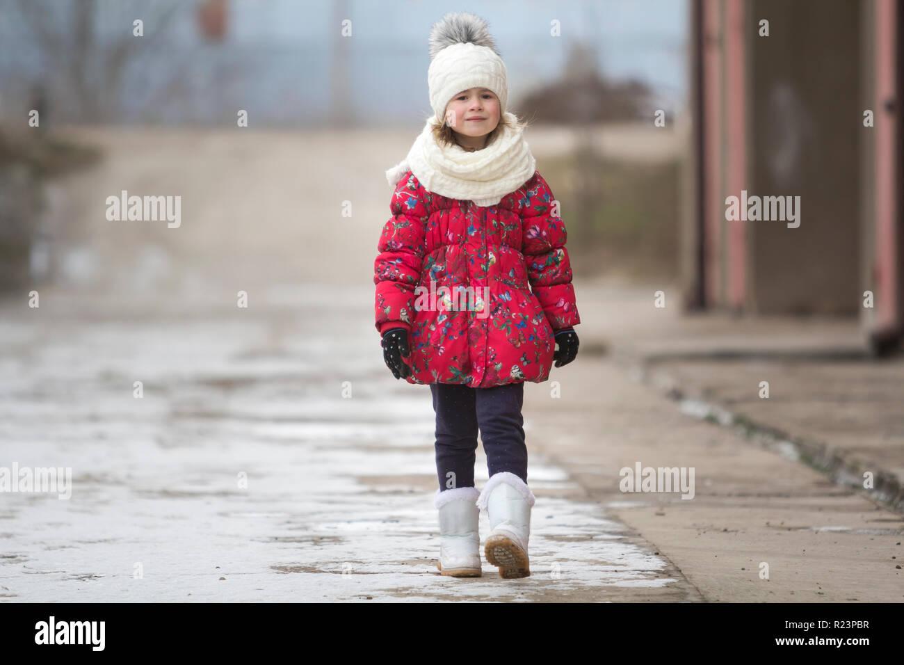 0898e4e373df Ritratto di piccolo grazioso funny giovane bambina carina ragazza in bello  e caldo abbigliamento invernale tranquillamente a piedi da soli su bianco  ...