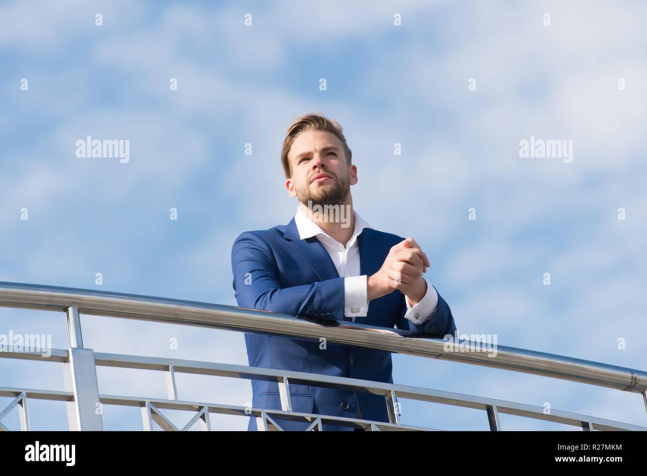 515618ac628f Uomo in abbigliamento formale sul piedistallo nuvoloso cielo blu.  Imprenditore fiducioso all'aperto. Guardando al futuro. Pensare a nuove  possibilità.