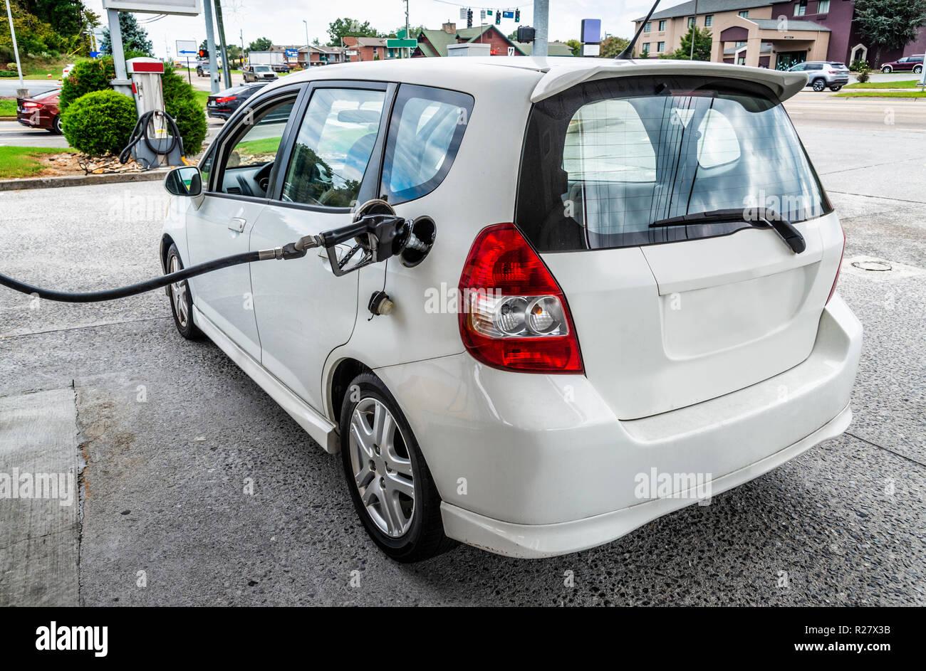 Angolo orizzontale shot dalla parte posteriore verso la parte anteriore di un generico piccola vettura bianca essendo riempito con benzina. Immagini Stock