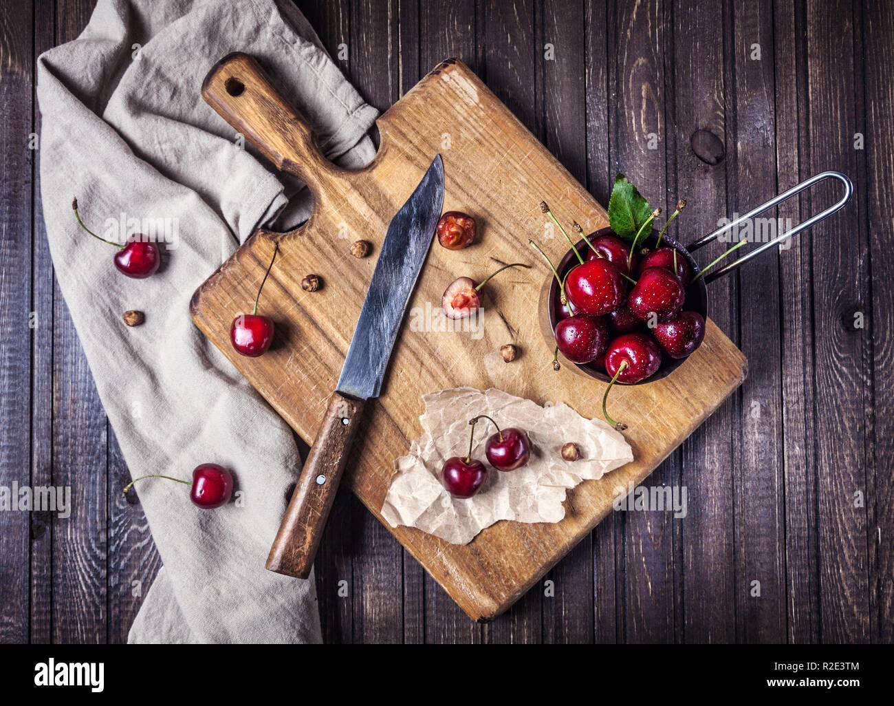 La ciliegia sulla scheda di taglio con il coltello sul tavolo di legno in cucina Immagini Stock