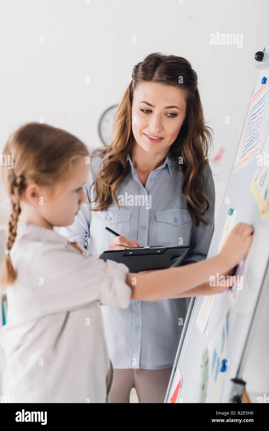 Psicologo sorridente con appunti e il bambino vicino a lavagna con vari disegni Foto Stock