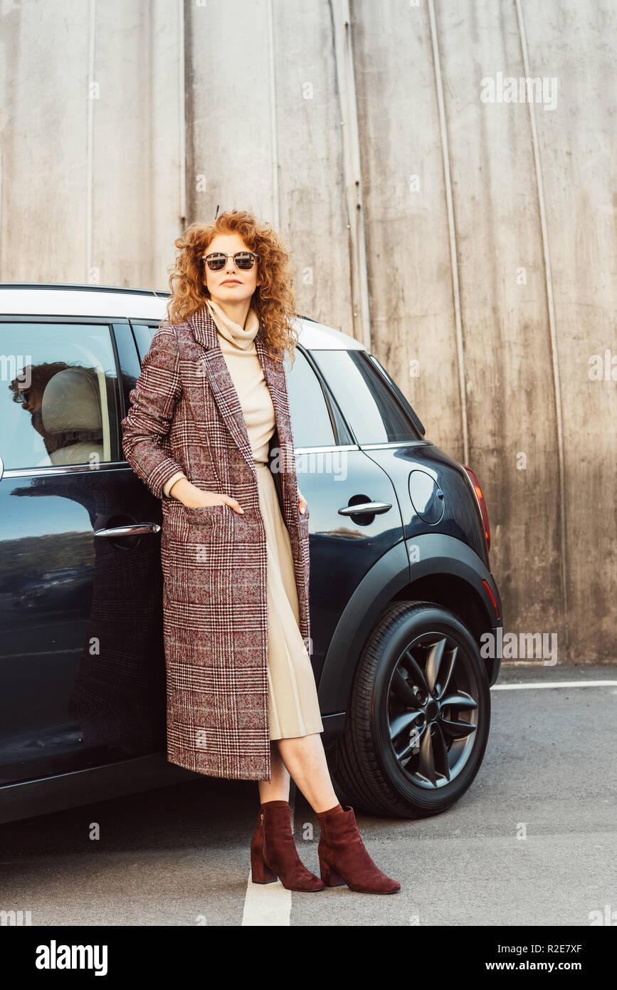 Femmina adulta del modello in cappotto e occhiali da sole in posa in  prossimità di auto 1a1ad044162e