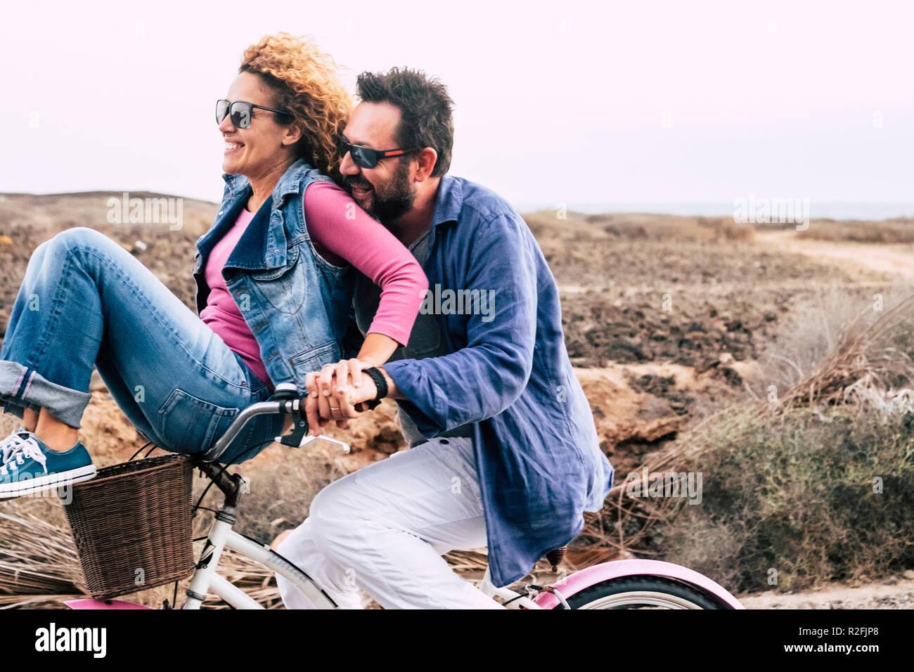 Adulto felice caucasici, giovane divertendosi con la bicicletta nel tempo libero attività. concetto di active giocoso persone con bici durante le vacanze - gioia quotidiana Stile di vita senza limitazioni di età - portare l uomo donna e tanto divertimento e ridere un sacco con il vento in aria Immagini Stock