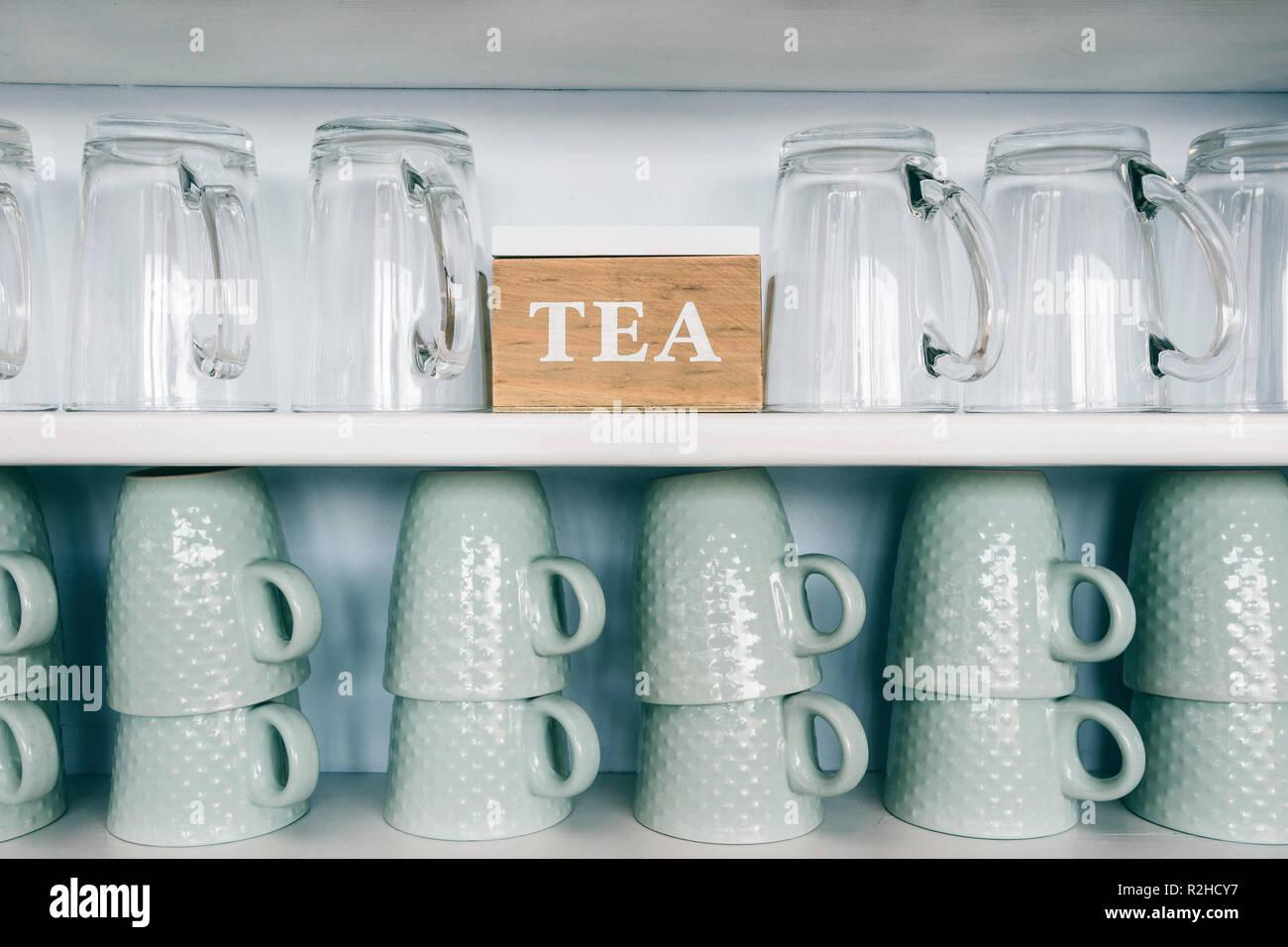 Tazze da tè e tazze da caffè su una mensola da cucina con una ...