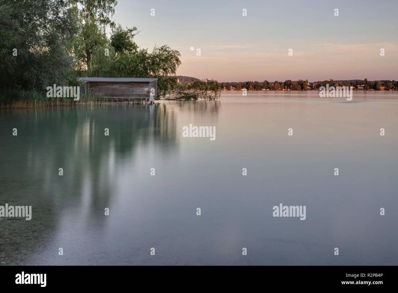 Una lunga esposizione di Wörthsee lago con barca casa al sorgere della luna (non ancora scuro) Immagini Stock