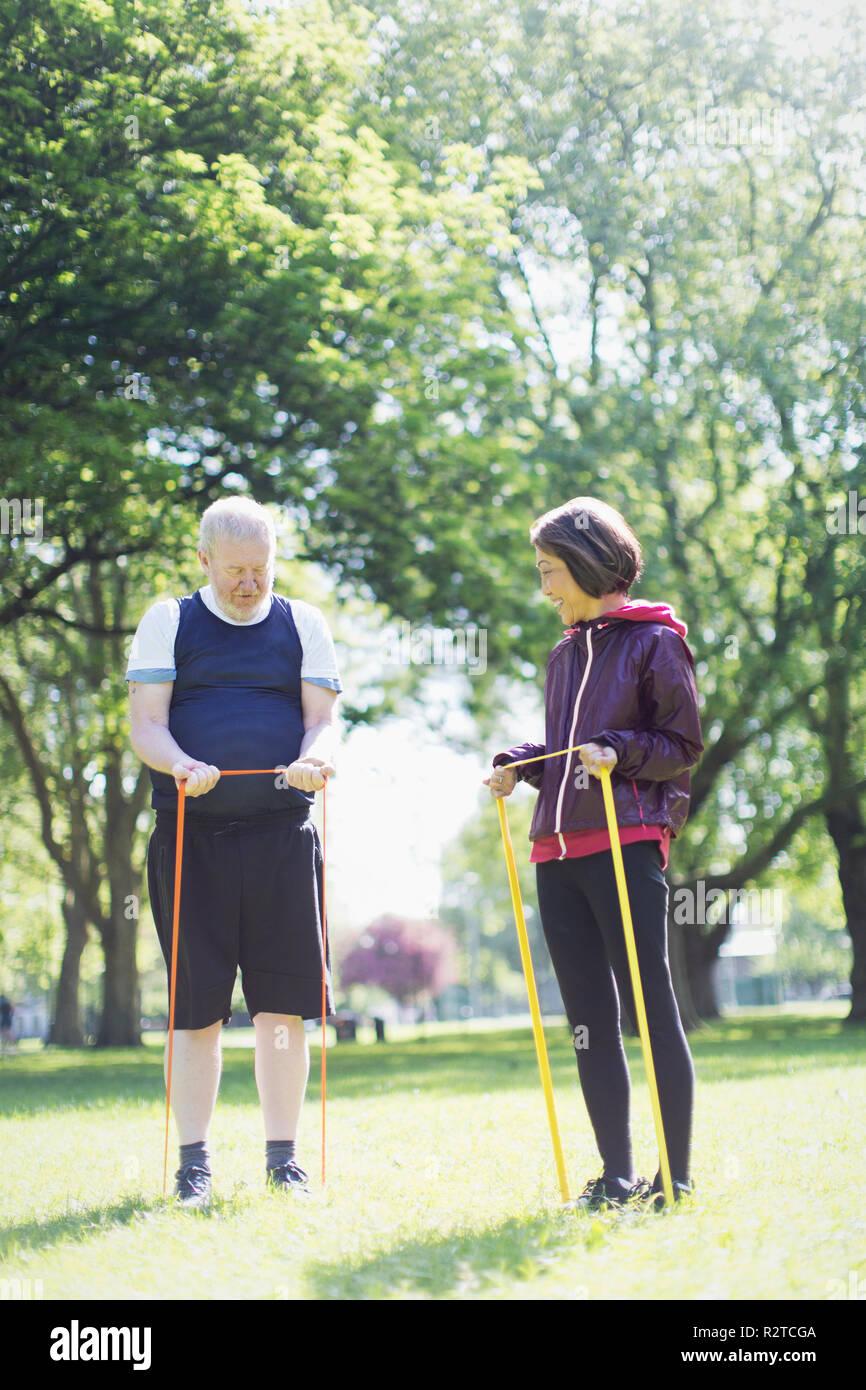 Attivo coppia senior esercitando, stretching con bande di resistenza nel soleggiato parco Immagini Stock