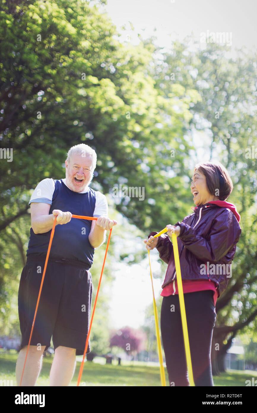Attivo entusiasta coppia senior esercitando, utilizzando bande di resistenza nel soleggiato parco Immagini Stock