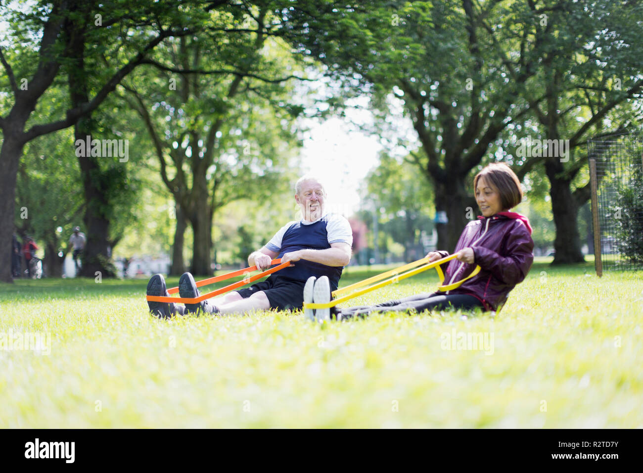 Attivo coppia senior esercitando, utilizzando bande di resistenza in posizione di parcheggio Immagini Stock