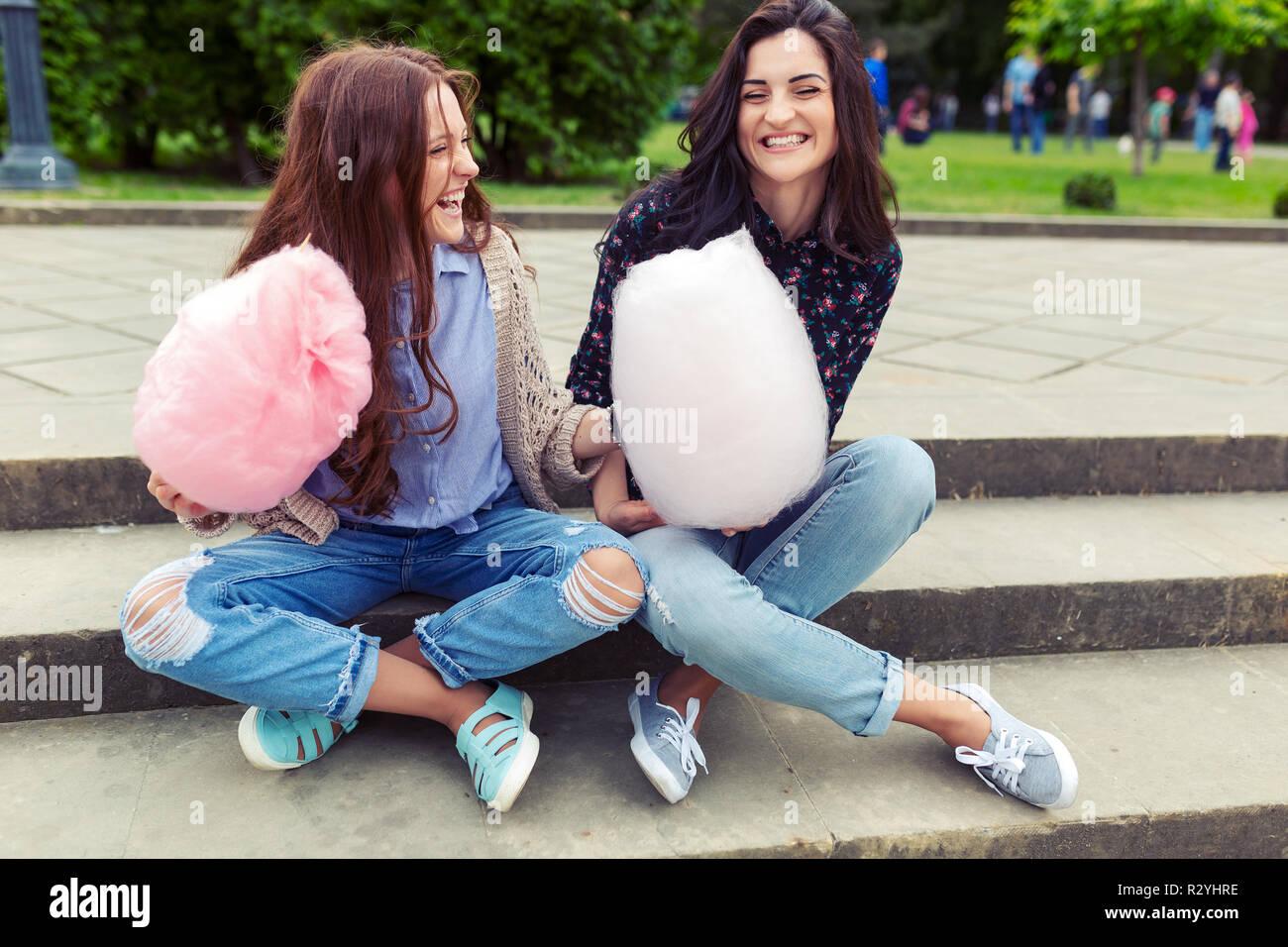 Giovane, allegro ragazze divertirsi con cotone candy all'aperto sul fondo urbano. Due sorelle facendo facce buffe e baffi durante la riproduzione e il mangiare Immagini Stock