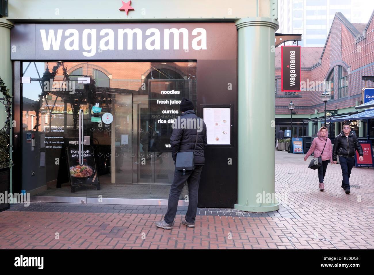 Un ristorante Wagamama anteriore che mostra chiaramente il ristorante distintivo delle catene di marca. Un potenziale cliente si erge al di fuori di studiare il menu Immagini Stock