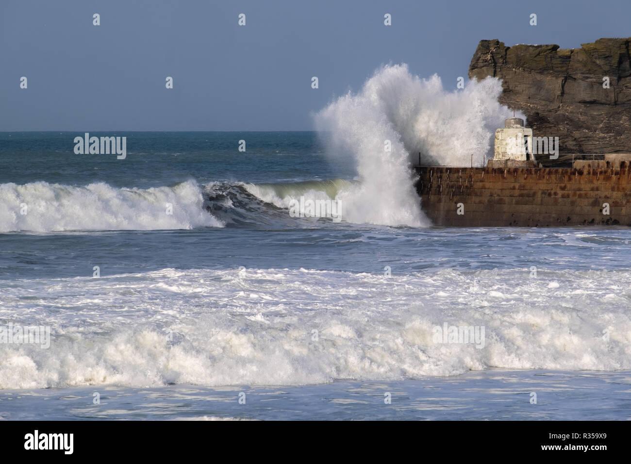 Unico surfer sfidando le onde vicino porto Portreath parete, Cornwall che si rompono sopra la parete del porto. Immagini Stock