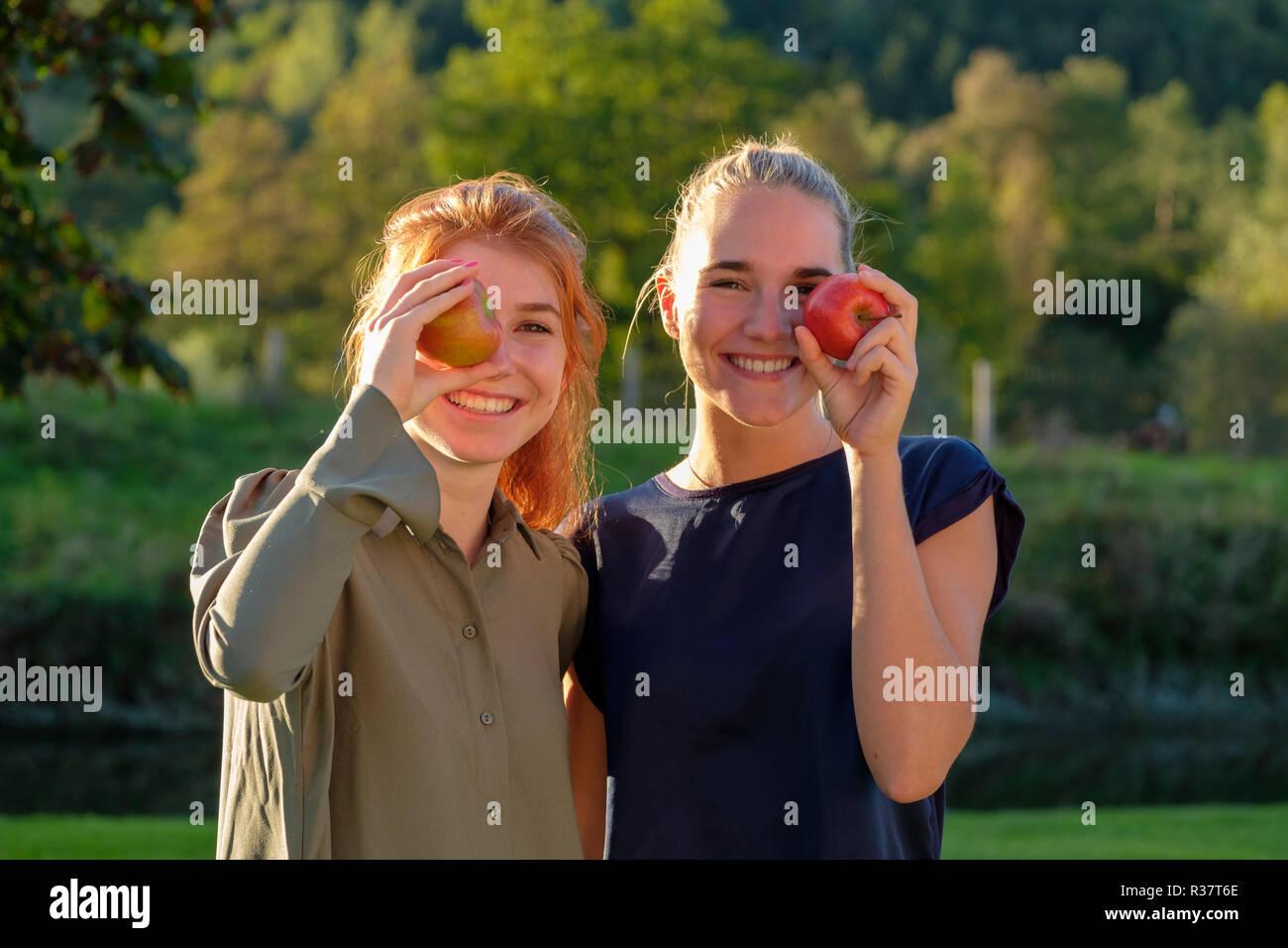 Due ragazze e giovani donne, ridendo di mangiare le mele, nel giardino, Alta Baviera, Baviera, Germania Immagini Stock