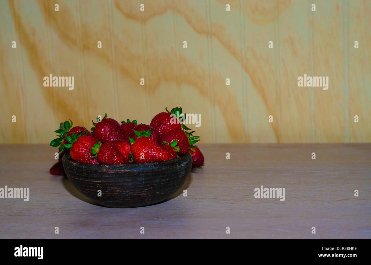 Fresas rojas maduras y frescas sobre vasija de greda Immagini Stock