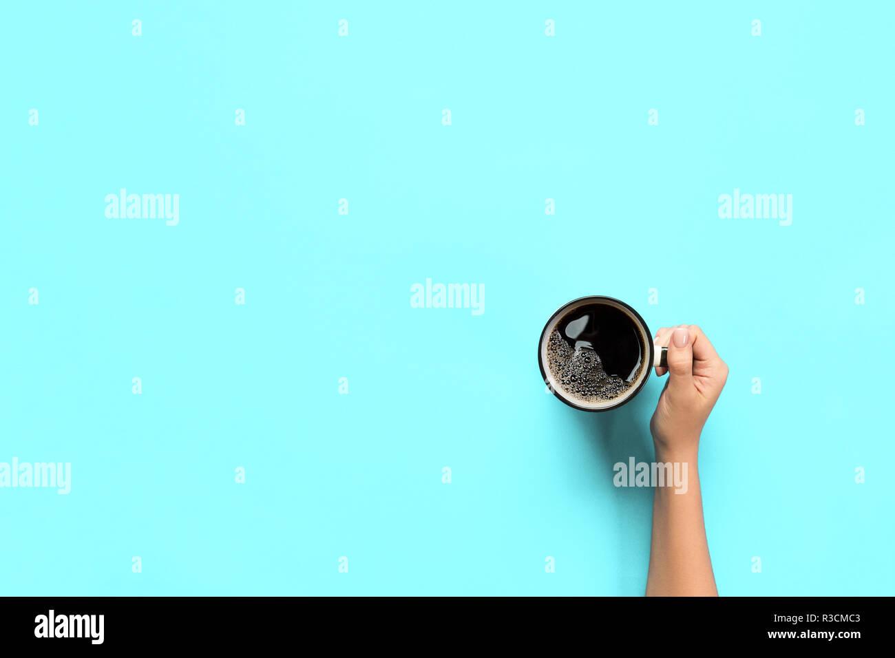 Stile minimalista donna mano che regge una tazza di caffè sul fondo. Appartamento laico, vista dall'alto. Immagini Stock