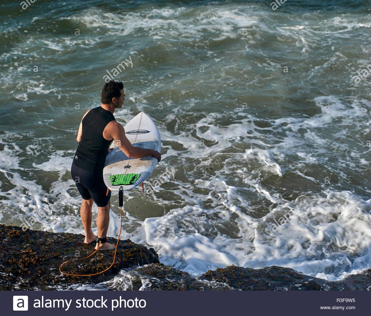 Un uomo con la sua tavola da surf, temporizzazione il suo ingresso per l'acqua da un roccioso promontorio; surf in spiaggia tornitori, Yamba, NSW, Australia. Immagini Stock