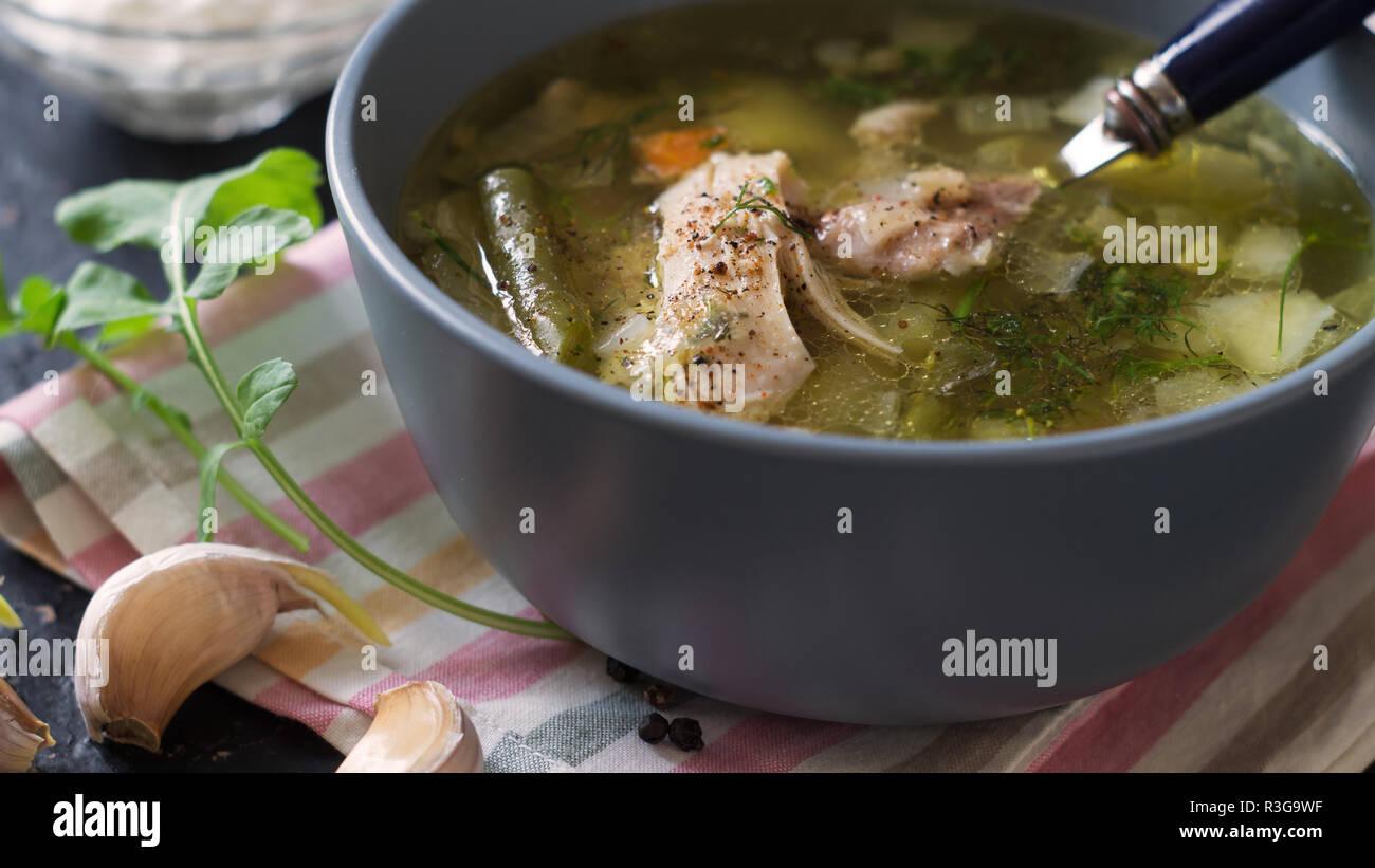 Primo corso. Zuppa di pollo e panna acida salsa su un tavolo scuro Immagini Stock