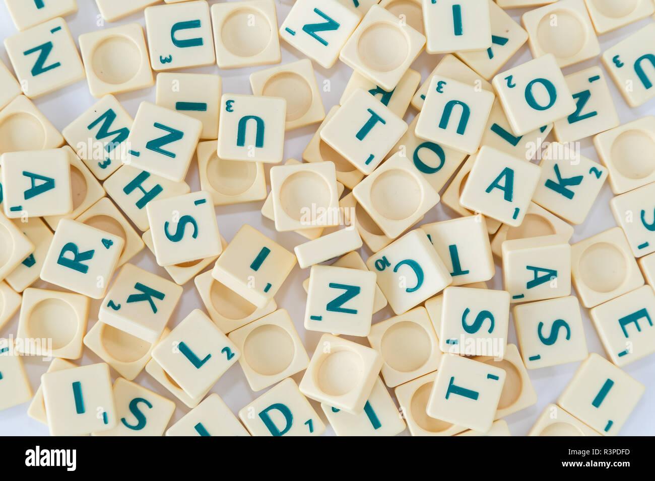 Pila di casuale gioco SCRABBLE lettera di piastrelle con valore di punteggio mescolato su sfondo, visto dall'alto. Foto Stock