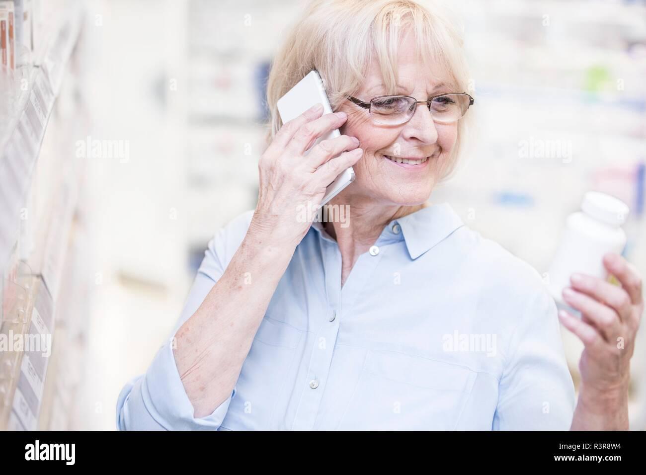 Senior donna discutendo la medicina sul telefono cellulare in farmacia. Immagini Stock