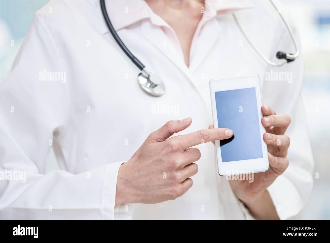 Medico puntando al telefono cellulare schermo. Immagini Stock
