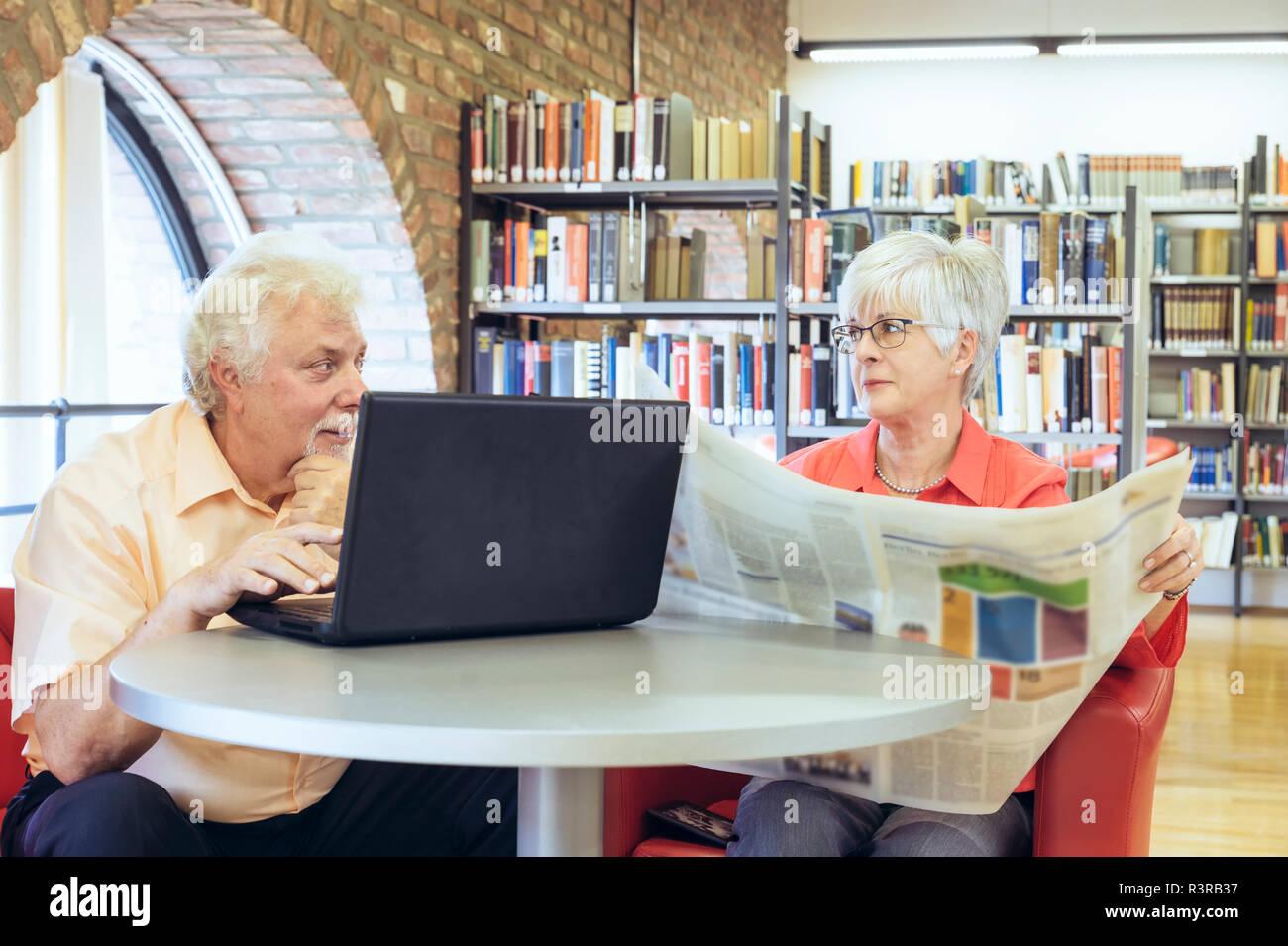Ein Seniorenpaar sitzen in einer Bücherei und kommunizieren über digitale Medien. Grevenbroich, Nordrhein-Westfalen, Deutschland Immagini Stock