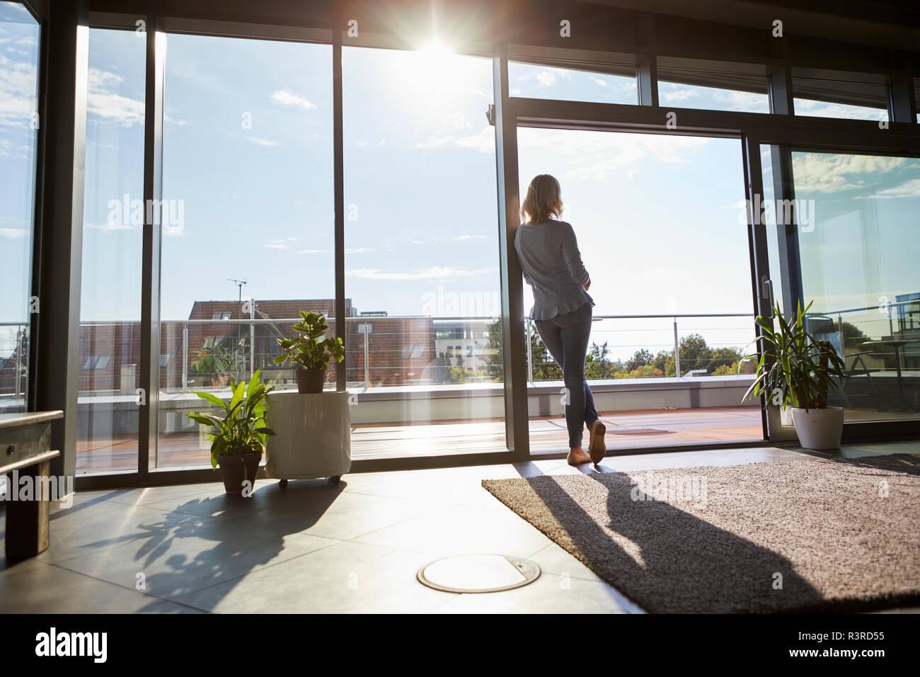 Vista posteriore della donna in controluce in piedi presso la finestra a casa guardando fuori Foto Stock