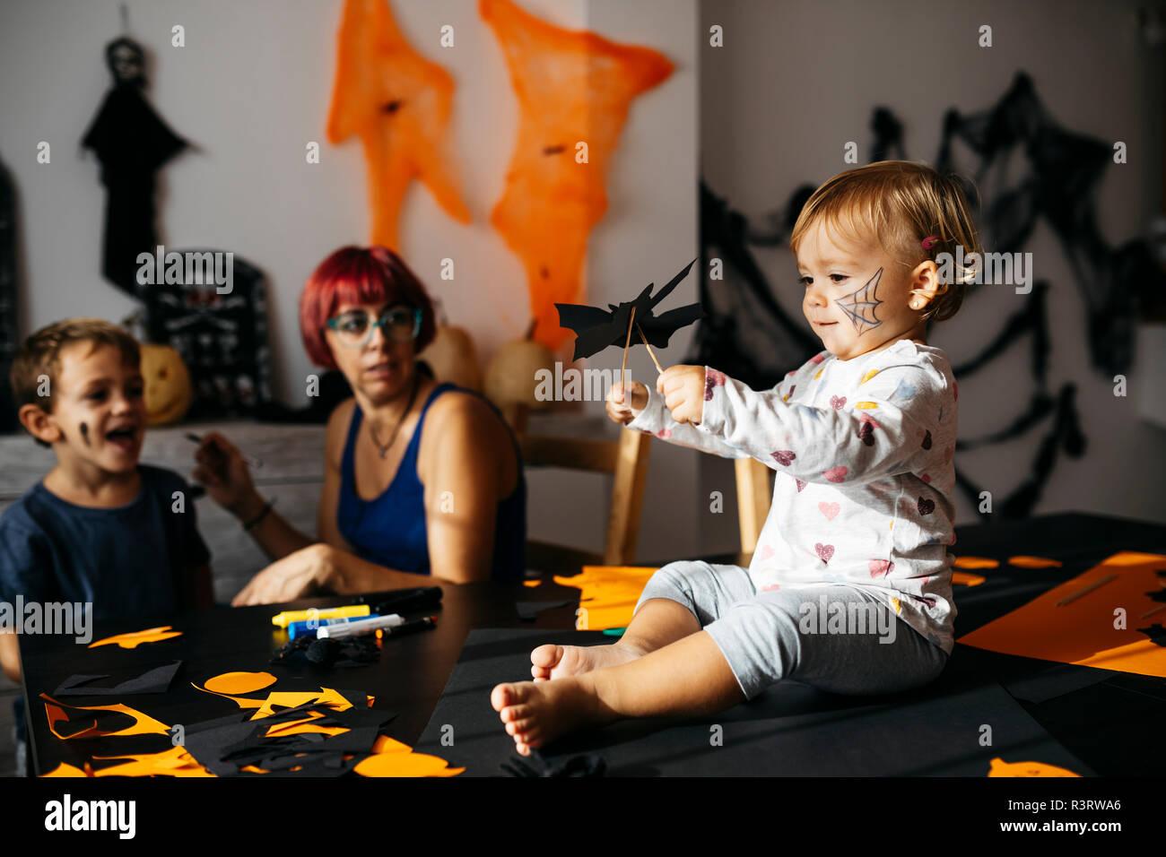 Baby girl giocando con decorazione di halloween a casa mentre la madre e il fratello osservando il suo Foto Stock