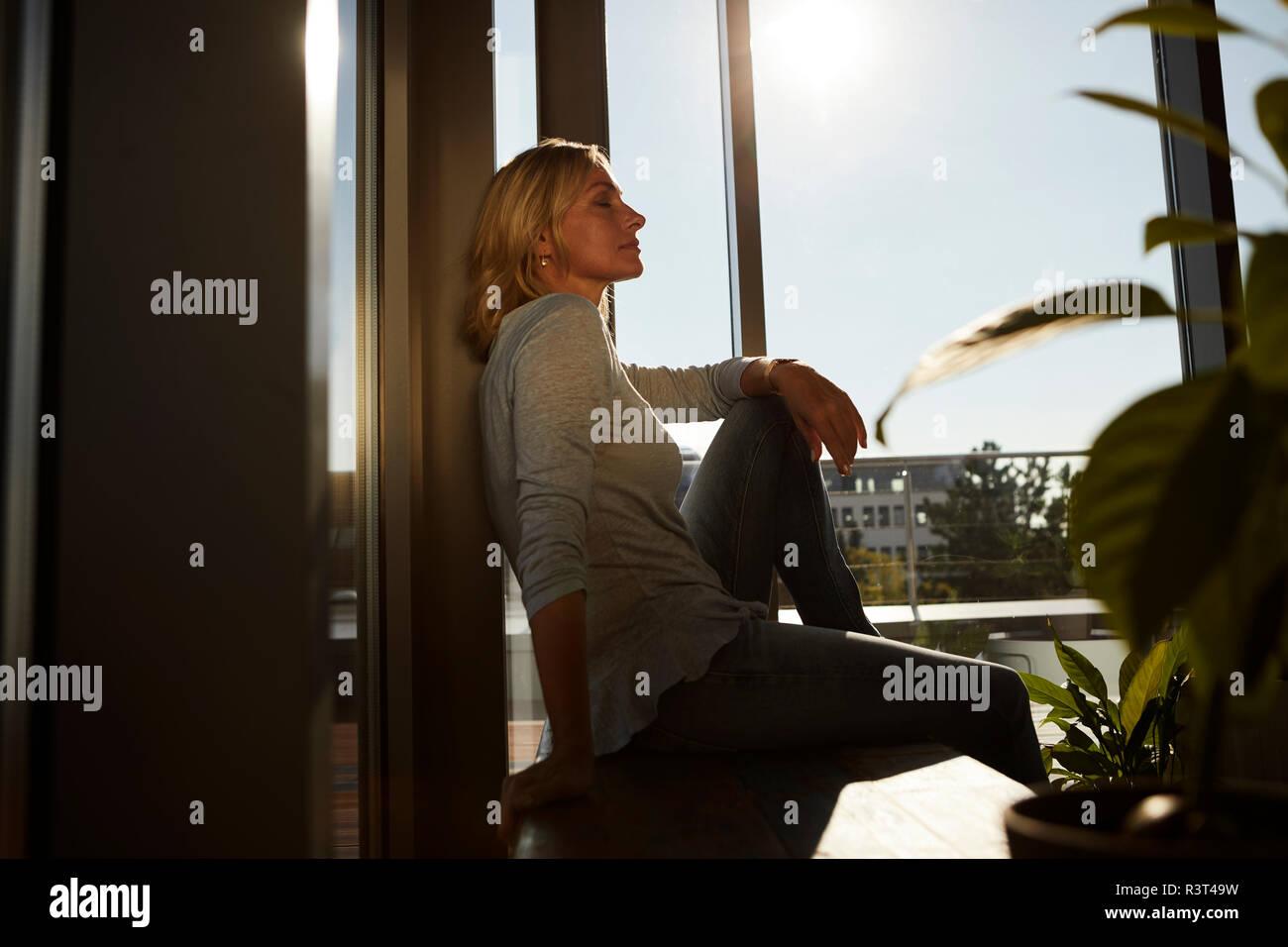 Rilassata donna matura seduta in presenza di luce solare a casa Foto Stock