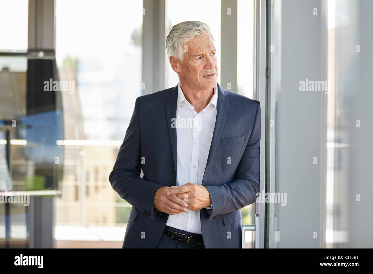 Imprenditore preoccupato in piedi dalla finestra, pensando Foto Stock