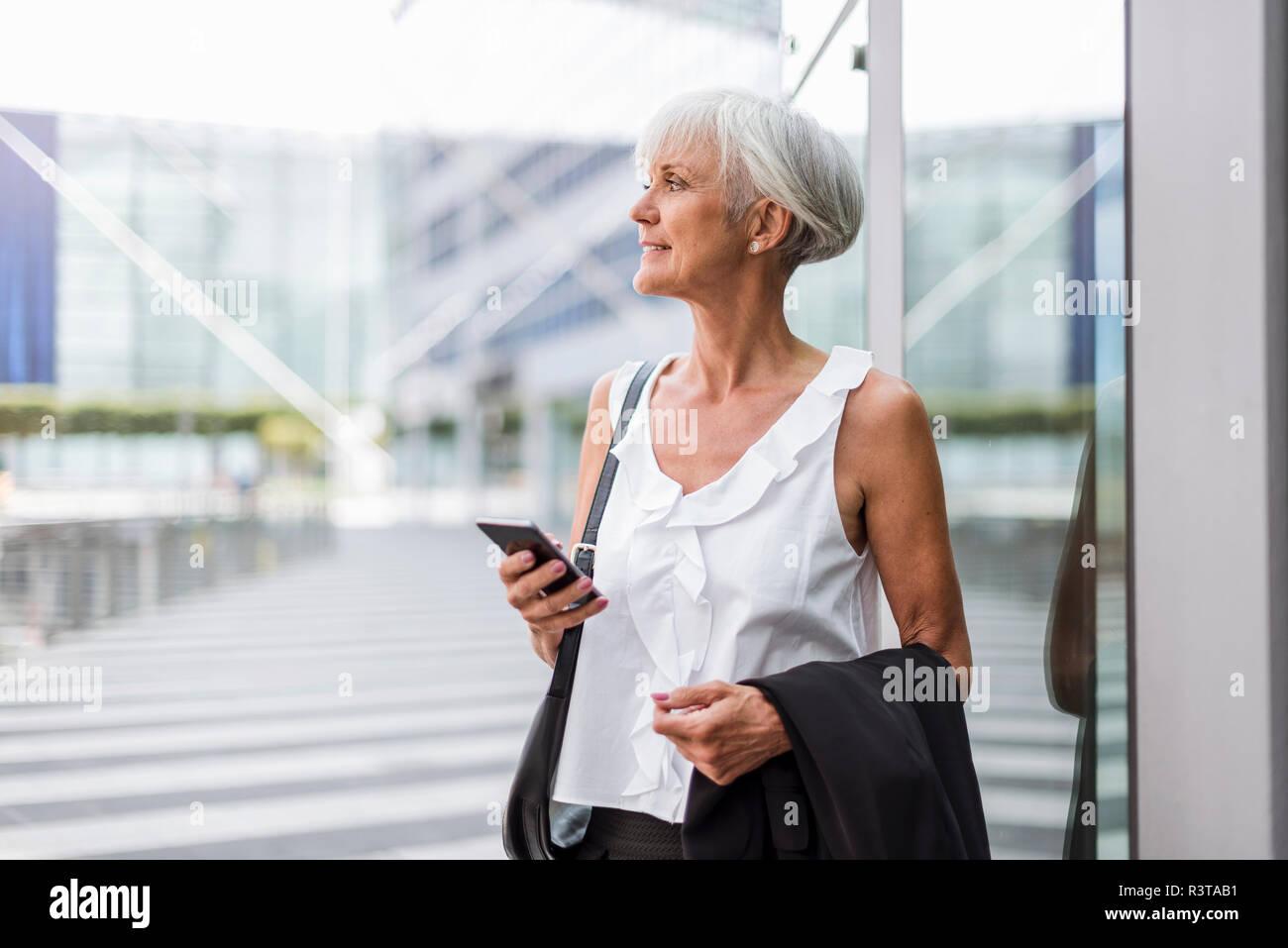 Donna senior con un telefono cellulare nella città guardando intorno Foto Stock