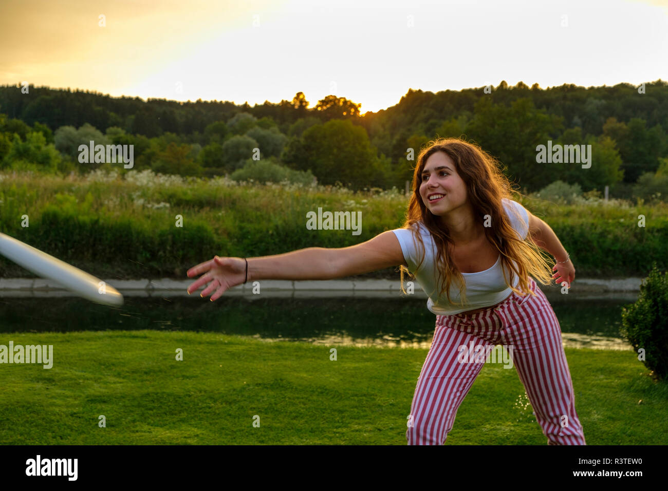 Giovane donna gettando flying disc Foto Stock