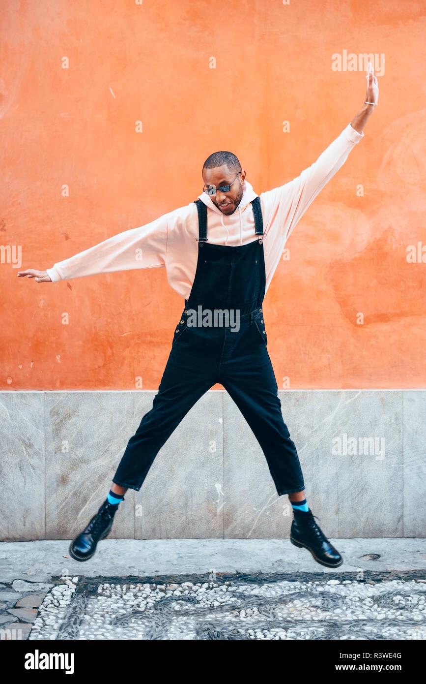 Giovane uomo nero indossando abiti casual jumping in background urbano. Il concetto di stile di vita. Millenaria ragazzo africano con bib pants all'aperto Foto Stock