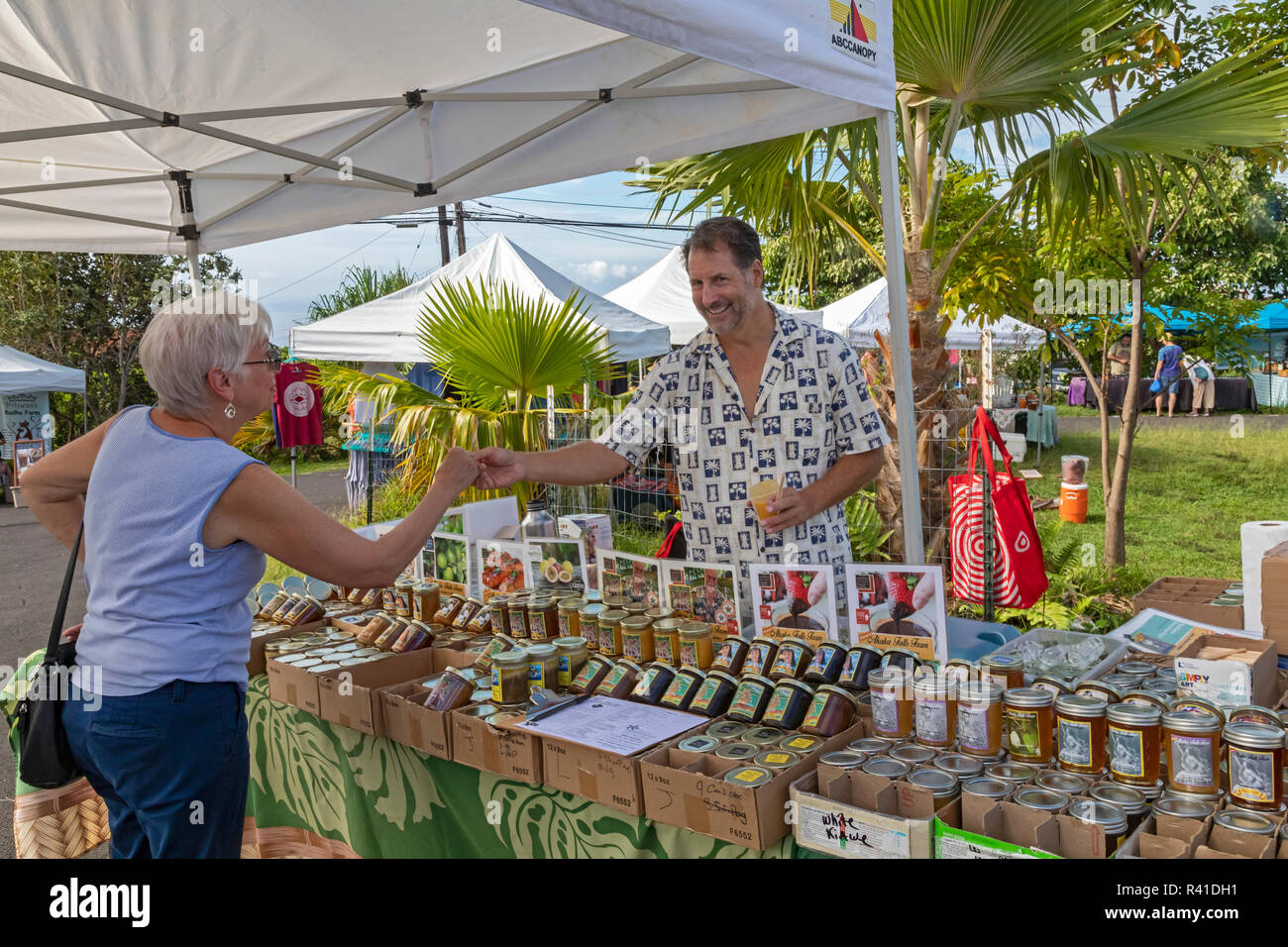 Il capitano Cook, Hawaii - un fornitore offre un assaggio di localmente-cresciute marmellata alla pura Kona Green Market. Immagini Stock