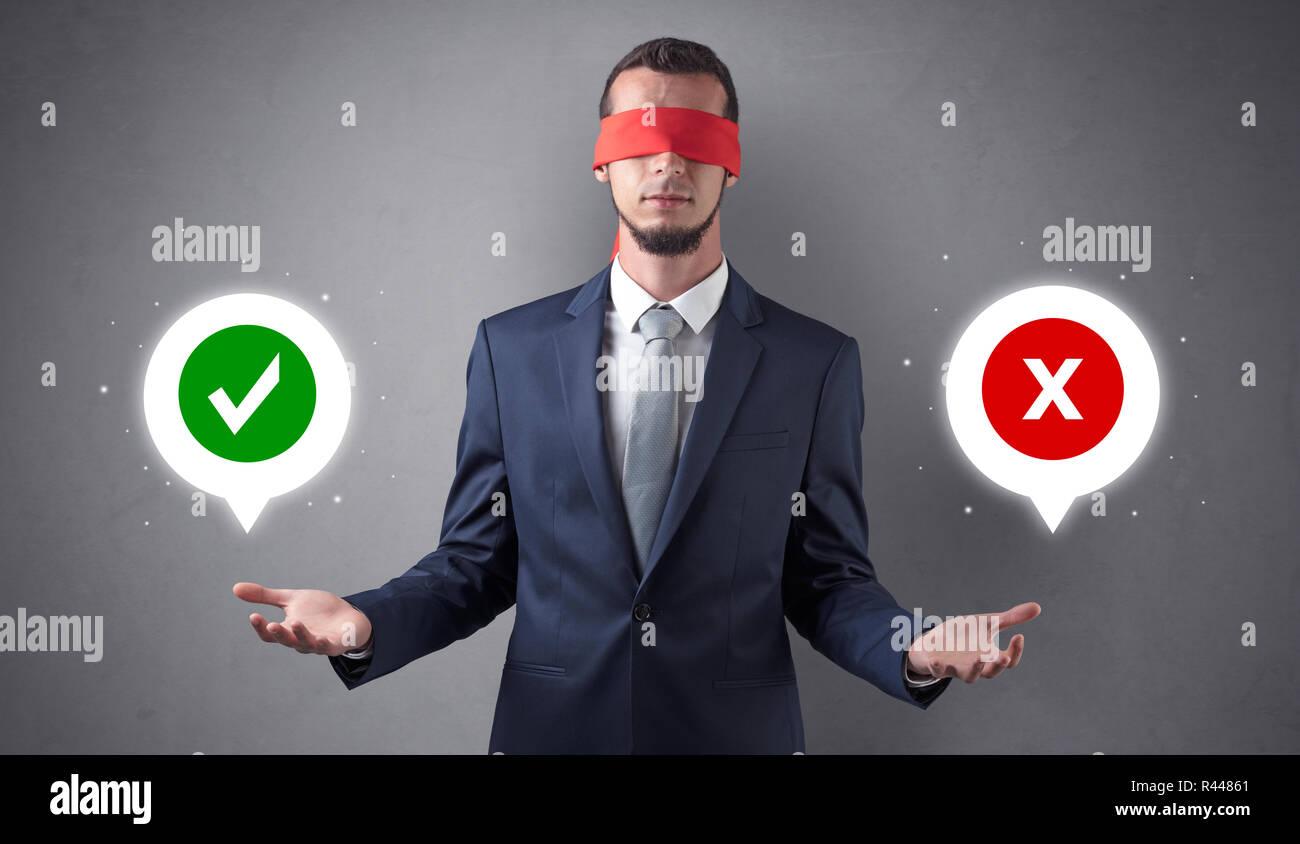 Gli occhi bendati imprenditore con verifica e x mark sopra la sua mano Immagini Stock