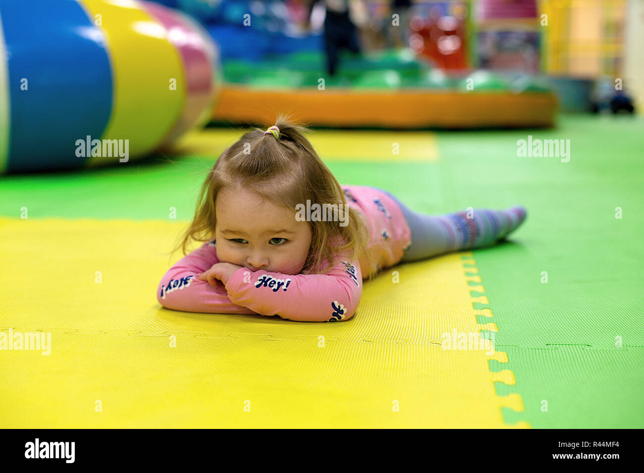 Annoiato giovane ragazza distesa sul pavimento a incastro mat in
