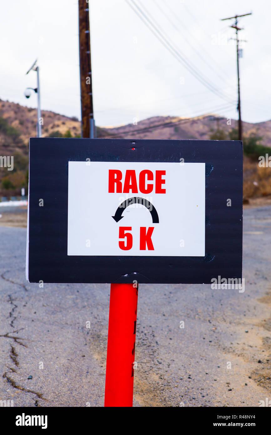 Esecuzione di corsa su strada U girare a segno 5K Immagini Stock