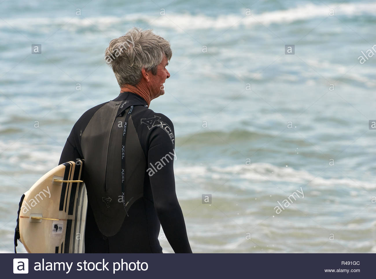 Un uomo di mezza età con capelli disordinati e nero muta, rilievi del rigonfiamento prima dell'immersione in con la sua tavola da surf; a tornitori Beach, Yamba, NSW, Australia. Immagini Stock