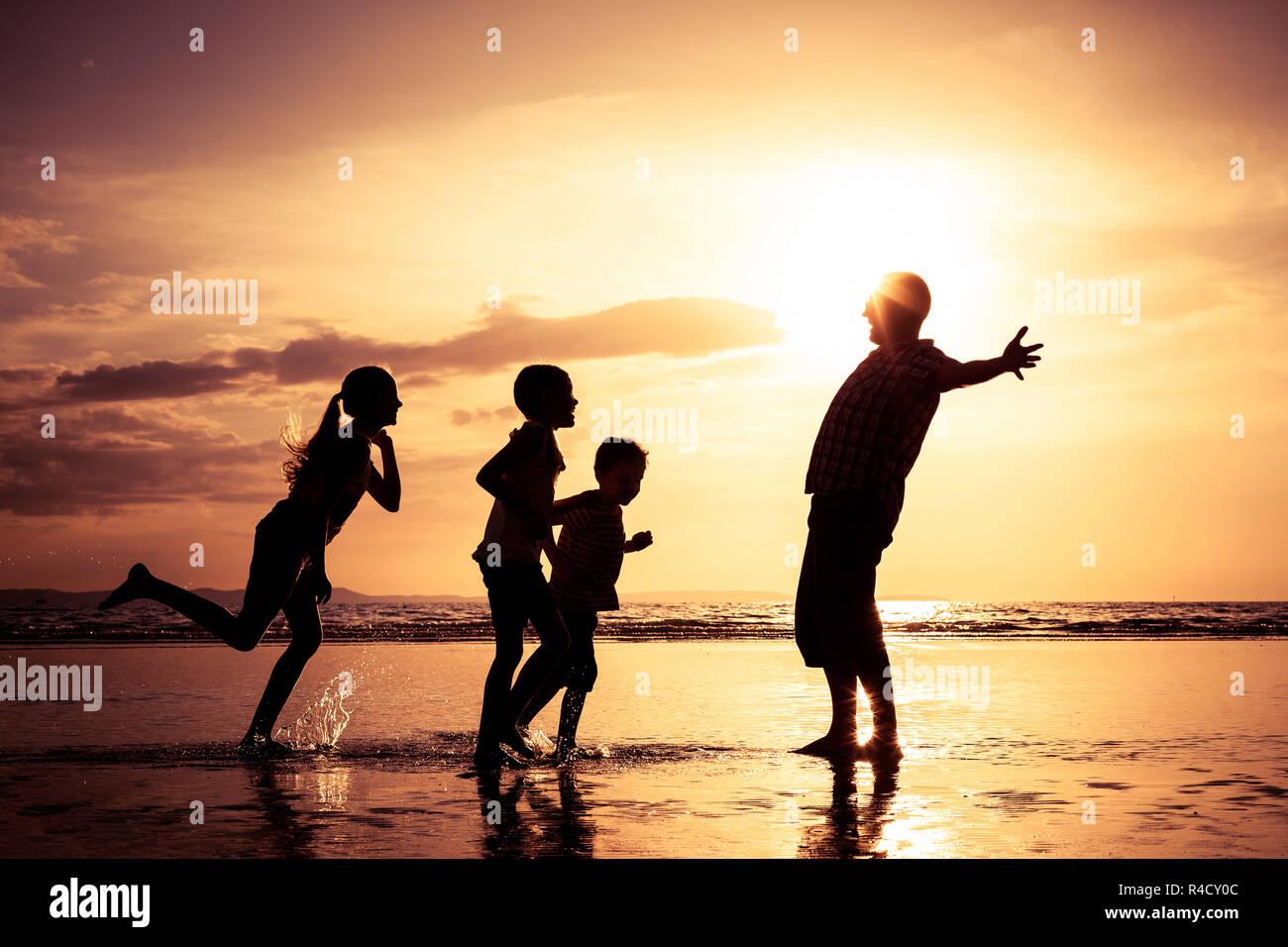 Padre e figli giocando sulla spiaggia al tramonto. Foto Stock