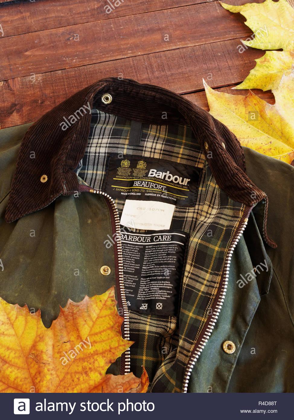 Ben indossato uomo verde Barbour giacca marrone su sfondo di legno con  foglie di autunno Immagini 14ae064d7583
