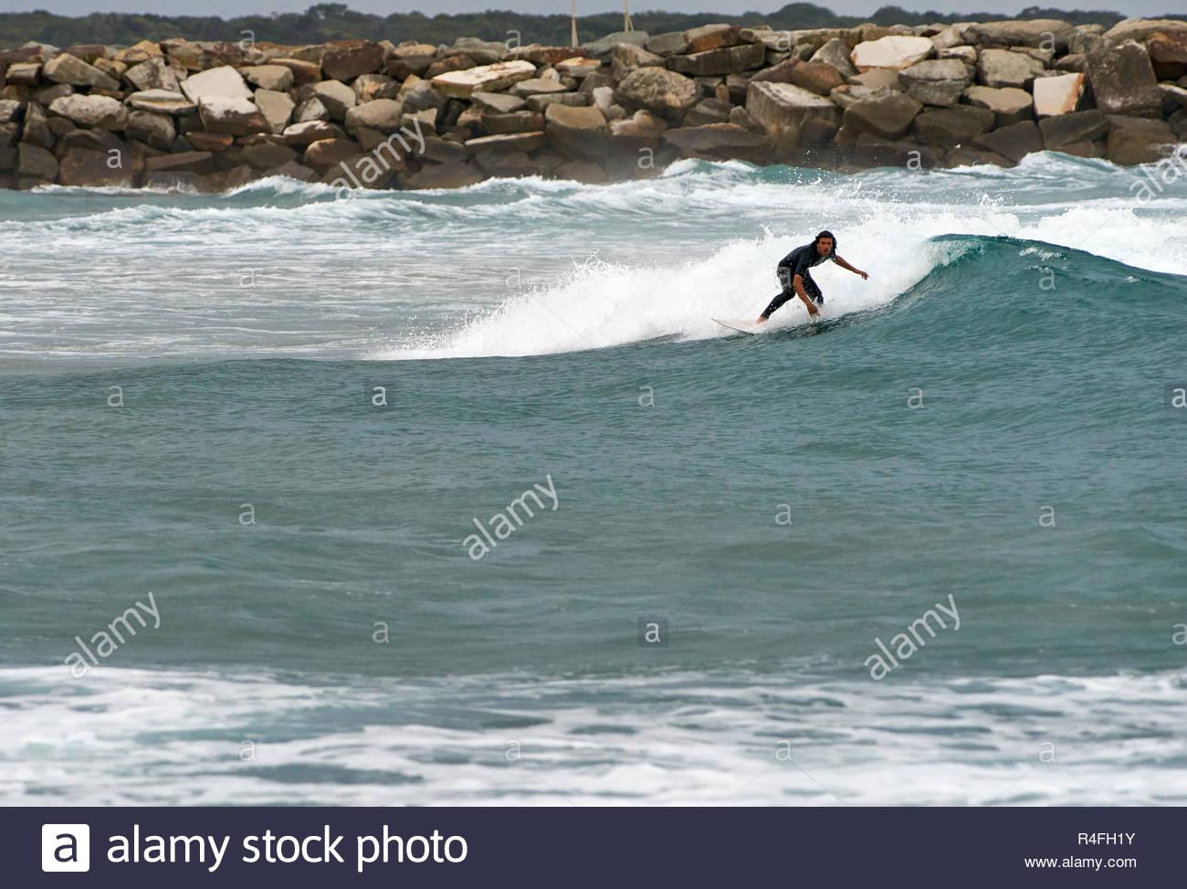 Un wet-adatto giovane maschio surfer preparando per il suo prossimo trucco frontside, navigando in piccola si gonfiano in prossimità di un break-parete; a Yamba, Australia. Immagini Stock