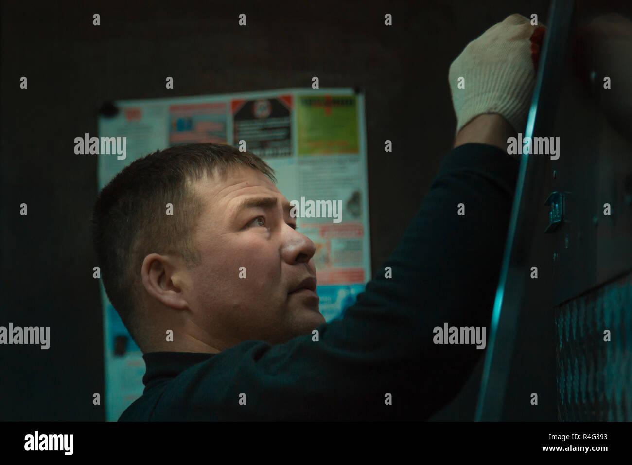 Ritratto di un giovane uomo in guanti durante il lavoro Immagini Stock