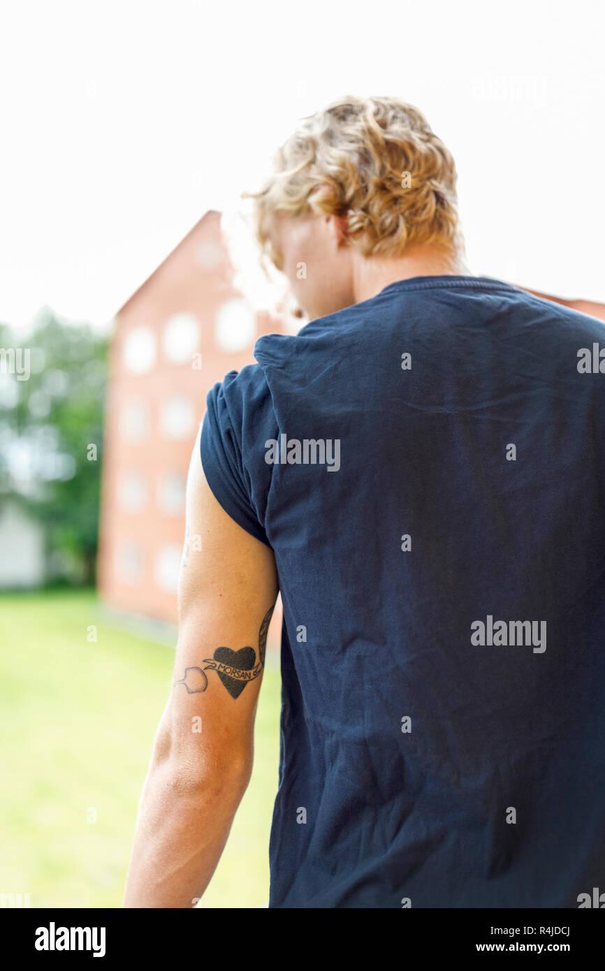 Vista posteriore del giovane uomo con tatuaggio sul braccio in Finspang df0653e6694f