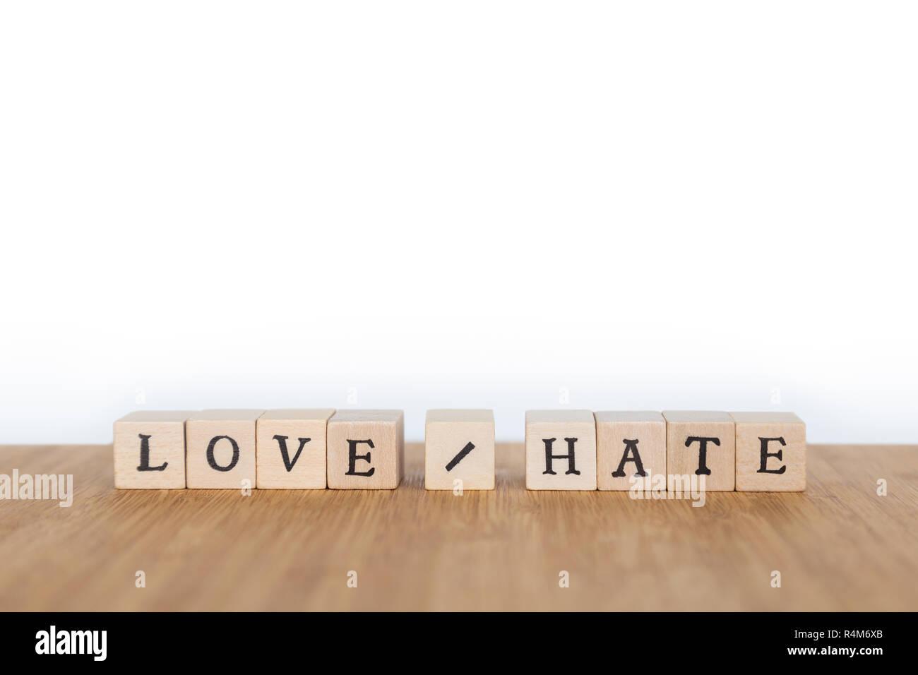 """Focus sulle parole """"Amore / Odio' fatta di blocco di legno dice con lettere su una tavola di legno. Profondità di campo. Copia dello spazio. Immagini Stock"""