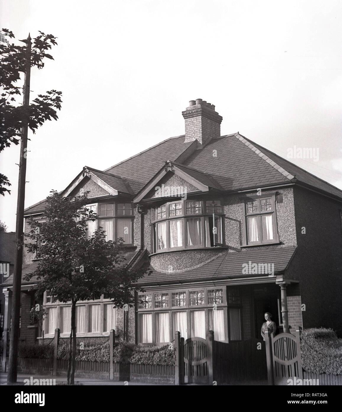1940s, storico, una signora in piedi all'ingresso di un semi-detached casa a due piani casa suburbana, Inghilterra, Regno Unito. Costruito negli anni Venti del Novecento, la casa aveva una scatola di legno le finestre a battente e un Pebble Dash esterno. Foto Stock