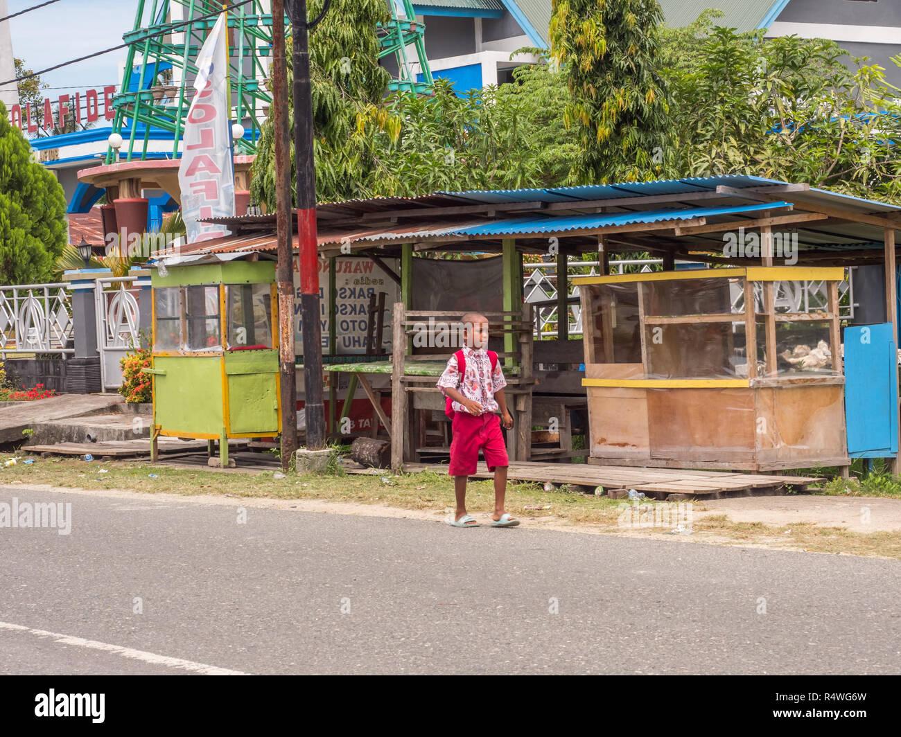 Kaimana, Indonesia - 31 Gennaio 2018: un gruppo di indonesiano, bambini in blu e rosso uniforme di camminare sulla strada in un piccolo villaggio della West Immagini Stock
