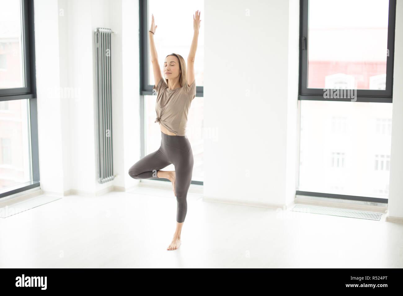 Atleta in piedi in posizione di yoga con bracci sollevati Foto Stock