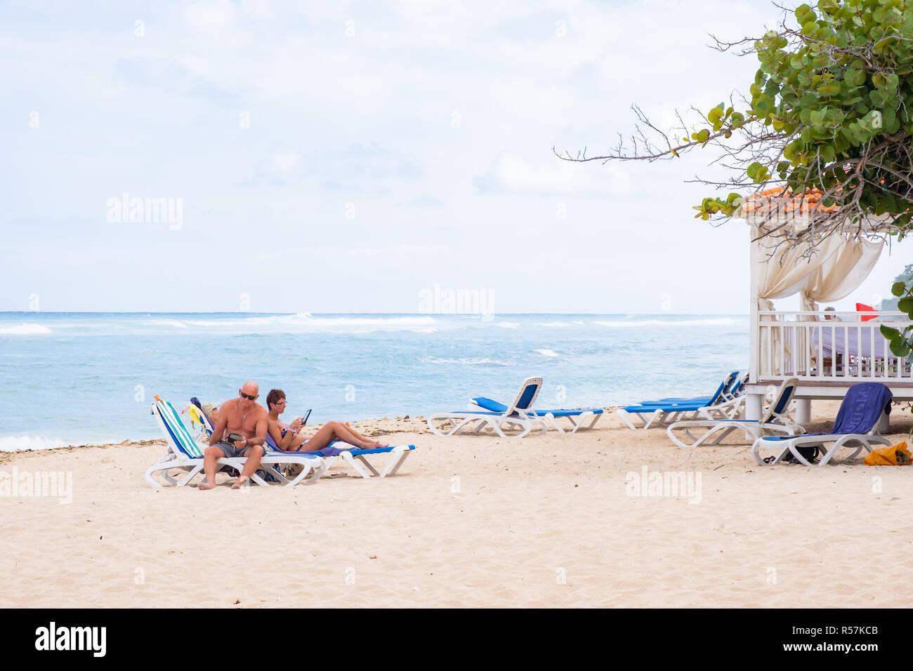 I turisti salotto sulla spiaggia a Cuba in anticipo di una tempesta. Immagini Stock