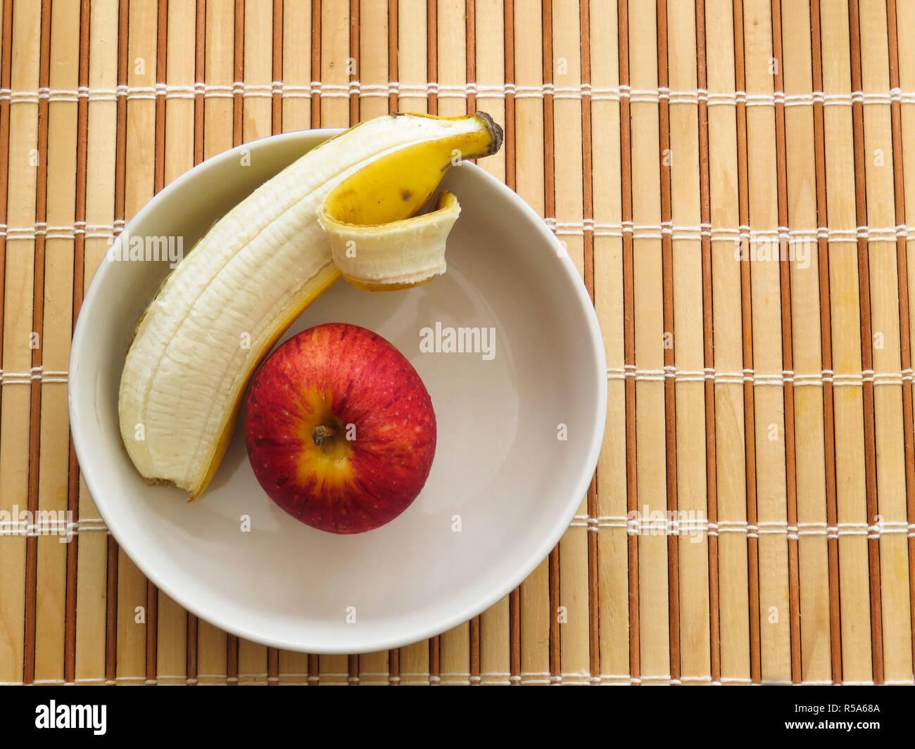 Mela e banana all'interno della vaschetta sul tavolo di legno Immagini Stock