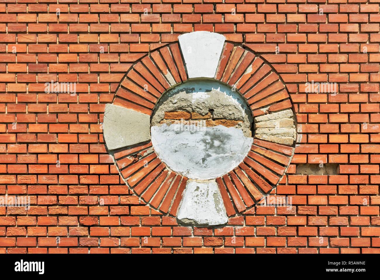 Vista in dettaglio di un muro di mattoni. Nel centro è un foro rotondo. Immagini Stock